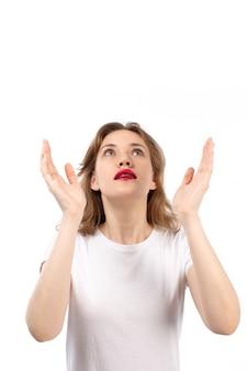 Una giovane signora di vista frontale nella posa bianca della maglietta sorpresa eccitata esaminando i cieli sul bianco