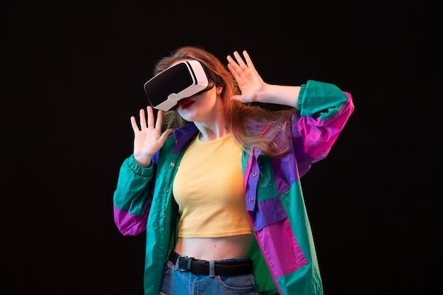 Una giovane signora moderna di vista frontale in maglietta arancione del cappotto variopinto che gioca e che prova vr sui giochi interattivi di gioco neri del fondo