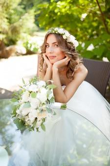 Una giovane sposa si siede a un tavolo di vetro con le mani piegate al mento