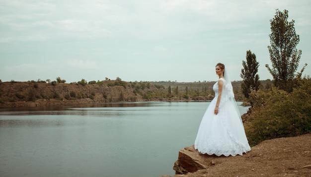 Una giovane sposa sorridente e bella in un abito bianco in un fiume o lago