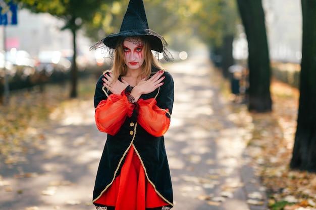 Una giovane strega si trova in strada con le braccia incrociate sul petto.