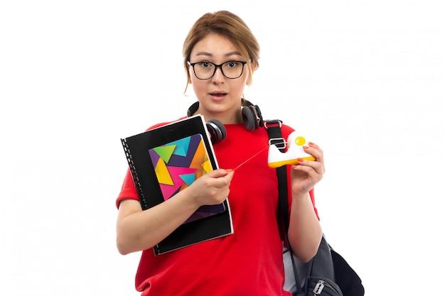 Una giovane studentessa di vista frontale in jeans neri della maglietta rossa che indossa le cuffie nere che tengono i quaderni sul bianco