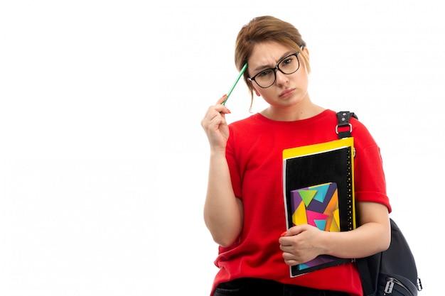 Una giovane studentessa di vista frontale in jeans neri della maglietta rossa che tengono i quaderni e gli archivi differenti che tengono matita che pensa sul bianco