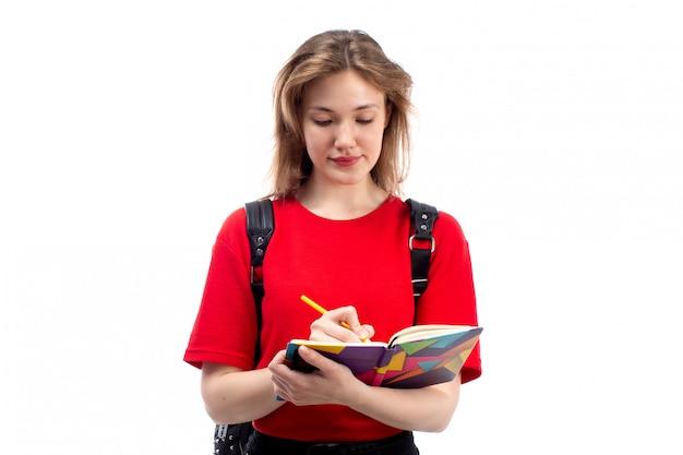 Una giovane studentessa di vista frontale negli archivi rossi dei quaderni della tenuta della borsa del nero della camicia che sorride annotando sul bianco