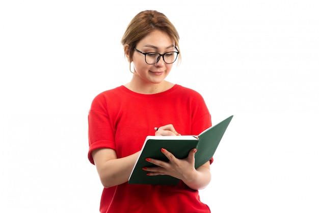 Una giovane studentessa di vista frontale nel quaderno rosso della tenuta della maglietta che annota le note sul bianco