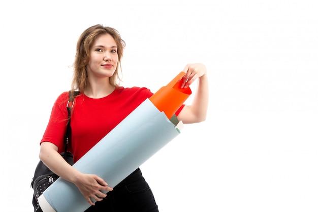 Una giovane studentessa di vista frontale nella borsa rossa del nero della camicia che sorride tenendo grande archivio sul bianco
