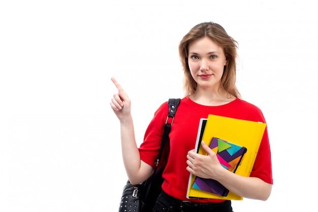 Una giovane studentessa di vista frontale nella posa rossa della penna e dei quaderni della borsa del nero della camicia rossa sul bianco