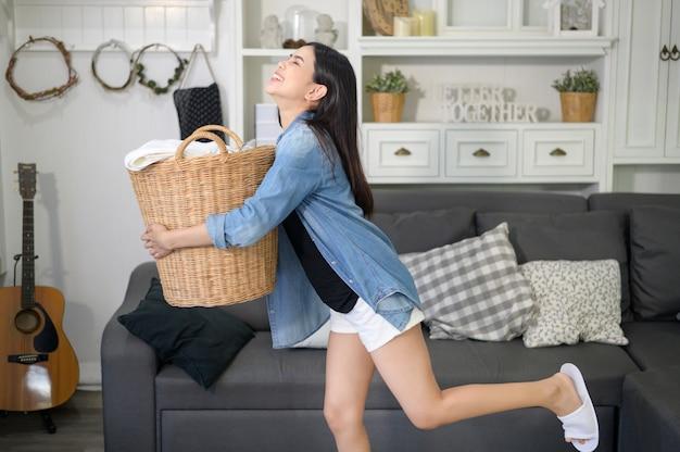 Una governante felice sta portando un secchio di panni per il bucato in casa.
