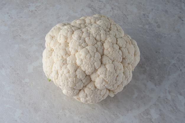 Una grande e fresca testa di cavolfiore su un marmo chiaro. la dieta.