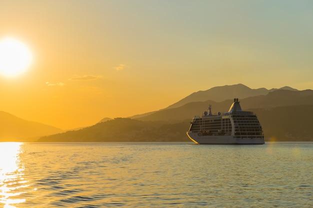 Una grande nave naviga sotto i raggi del tramonto lungo la baia di boka kotorska. montenegro.