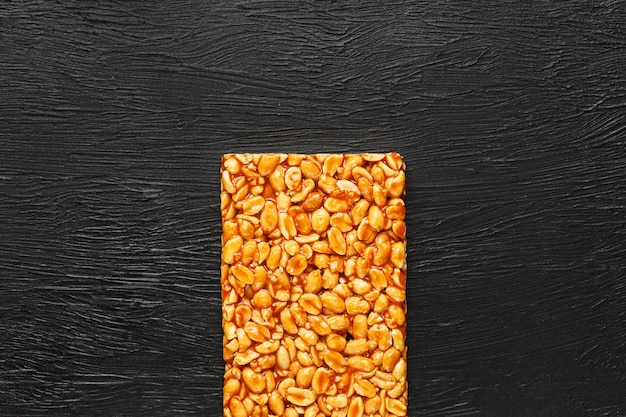 Una grande piastrella dorata di arachidi, una barra in una melassa dolce. kozinaki utili e gustosi dolci d'oriente