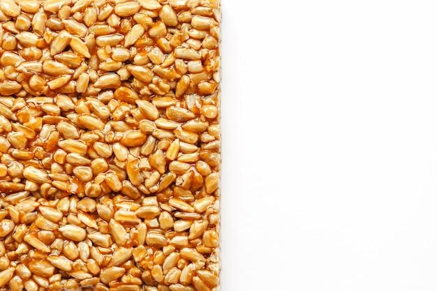 Una grande piastrella dorata di semi di girasole, una barra in una melassa dolce. kozinaki utili e gustosi dolci d'oriente