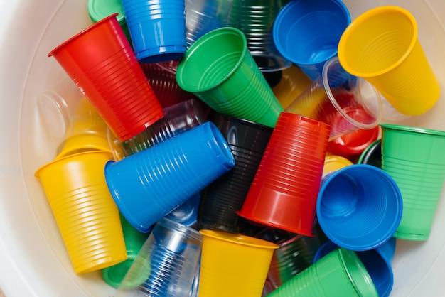 Una grande pila di bicchieri di plastica multicolori sparsi sul pavimento. inquinamento ambientale da rifiuti umani.