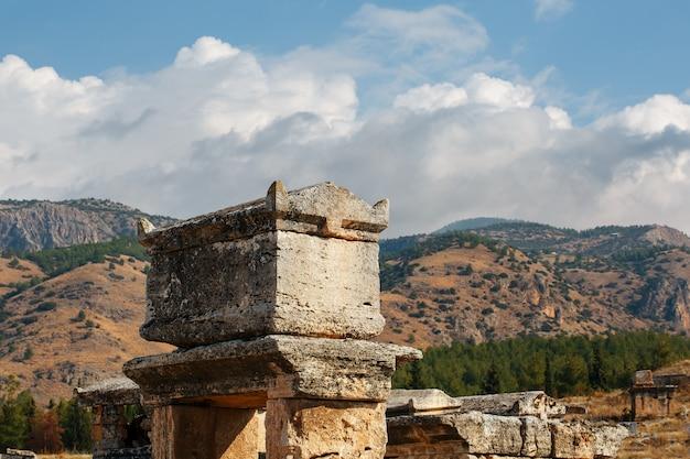 Una grande tomba di pietra contro montagne e cielo in un grande cimitero di hierapolis.
