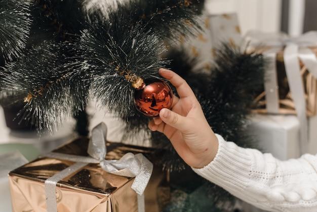 Una h in un maglione lavorato a maglia bianco appende una palla di natale rossa sul ramo di un albero di natale artificiale. decorare l'albero di natale con i giocattoli.