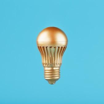 Una lampada a led dorata si libra sul blu.
