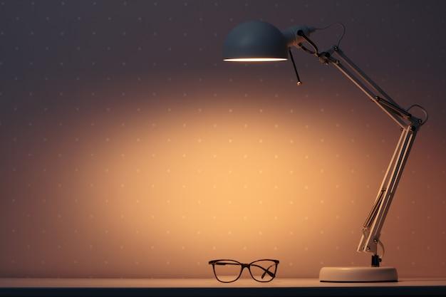 Una lampada da lavoro brilla di notte su un tavolo con gli occhiali.