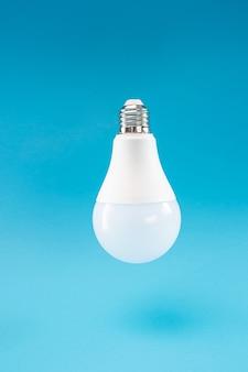 Una lampada led bianca su sfondo blu sembra sospesa nell'aria, per effetto della levitazione. sfondo blu, copia spazio, minimalismo.