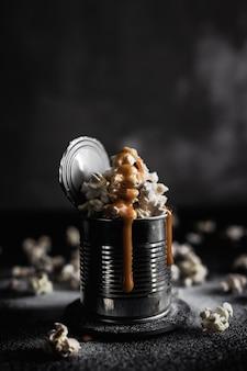 Una lattina d'acciaio di popcorn al caramello salato su sfondo scuro, foto lunatica