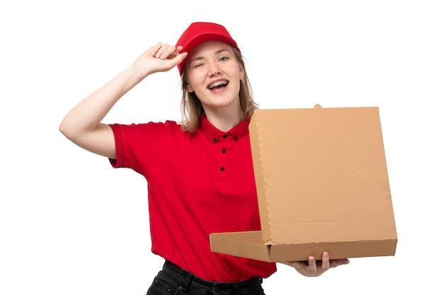 Una lavoratrice femminile del giovane corriere femminile di vista frontale della scatola sorridente della tenuta di servizio di distribuzione di alimenti con alimento su bianco