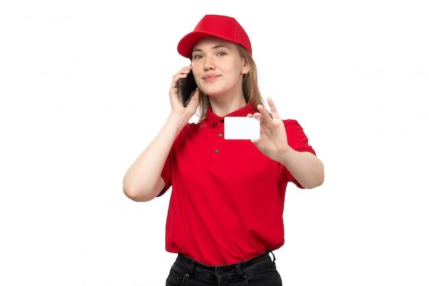 Una lavoratrice femminile del giovane corriere femminile di vista frontale di servizio di distribuzione di alimenti che parla sorridente sul telefono e che tiene carta bianca su bianco