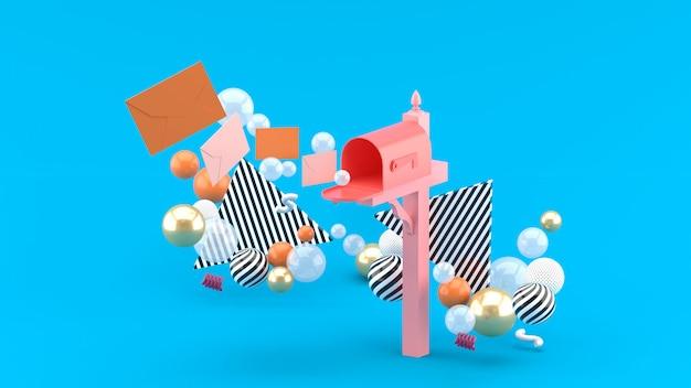 Una lettera galleggiante da una cassetta postale circondata da palline colorate su blu. rendering 3d.