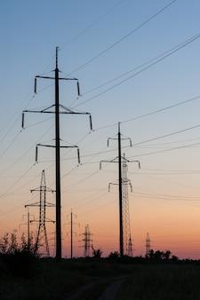 Una linea di pali con cavi ad alta tensione al tramonto