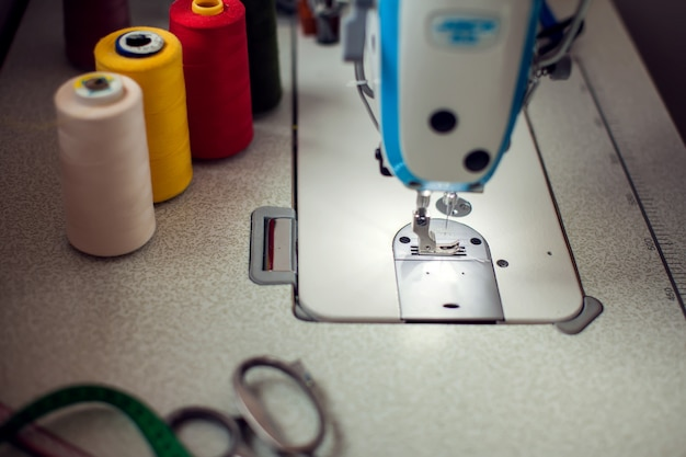 Una macchina da cucire con attrezzatura. produzione di abbigliamento e concetto di moda