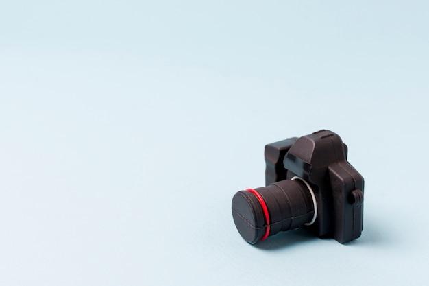 Una macchina fotografica nera artificiale su priorità bassa blu