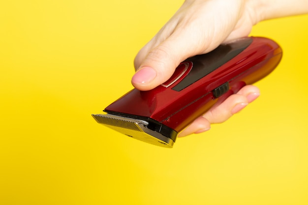 Una macchina per capelli meccanica macchina rosso scuro vista frontale in mano della giovane donna sull'attrezzatura gialla dello stilista di capelli del fondo