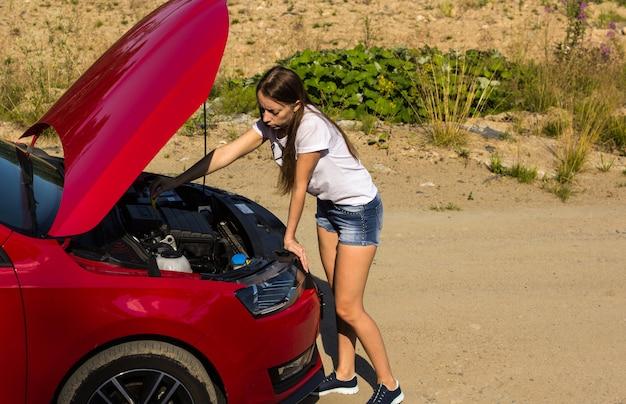 Una macchina rotta sulla strada, la ragazza controlla il livello dell'olio