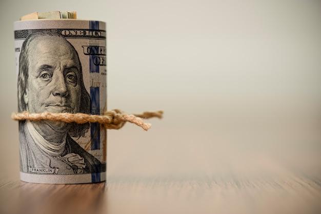 Una macro di un rotolo di 100 banconote del dollaro americano sullo spazio di legno della copia e del fondo