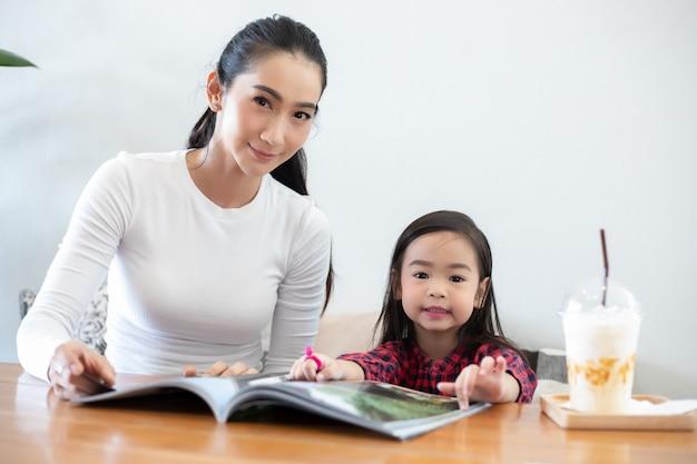 Una madre asiatica sta insegnando a sua figlia a leggere un libro durante la pausa del semestre sul tavolo vivente e sta mangiando latte freddo sul tavolo a casa. concetti e attività educative della famiglia