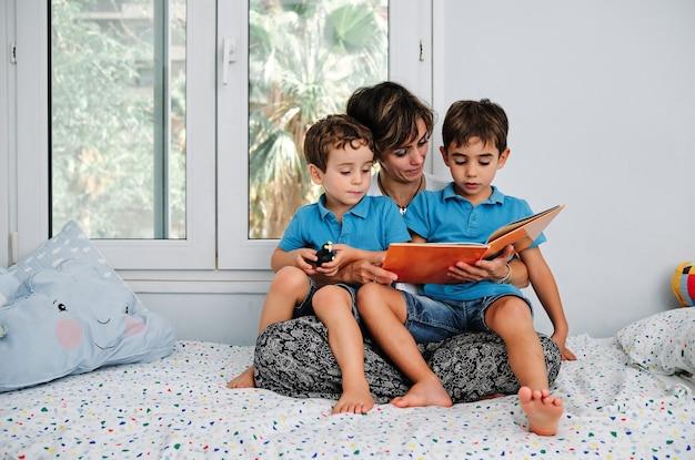 Una madre che legge un libro ai suoi figli piccoli