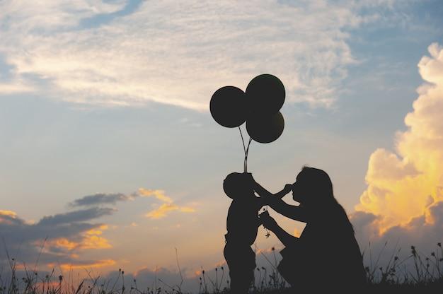 Una madre e un figlio che giocano all'aperto alla siluetta di tramonto