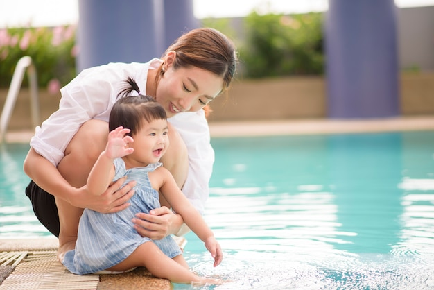 Una madre e una figlia asiatiche felici si divertono a nuotare in piscina, stile di vita, genitorialità, concetto di famiglia