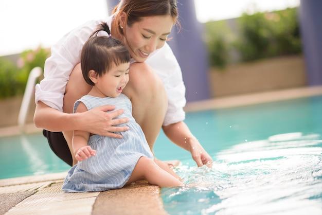 Una madre e una figlia asiatiche felici si divertono a nuotare in piscina