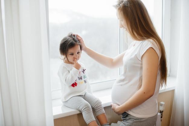 Una madre incinta è in piedi vicino alla finestra con la sua piccola figlia
