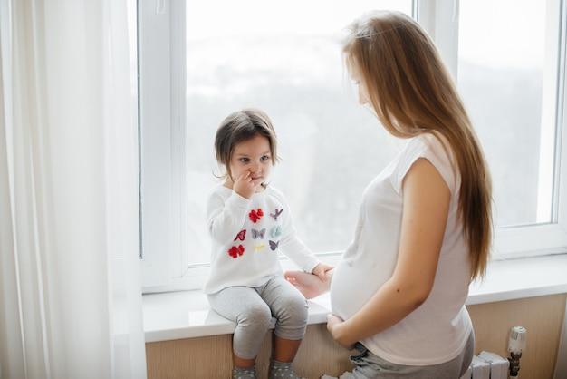 Una madre incinta è in piedi vicino alla finestra con la sua piccola figlia.