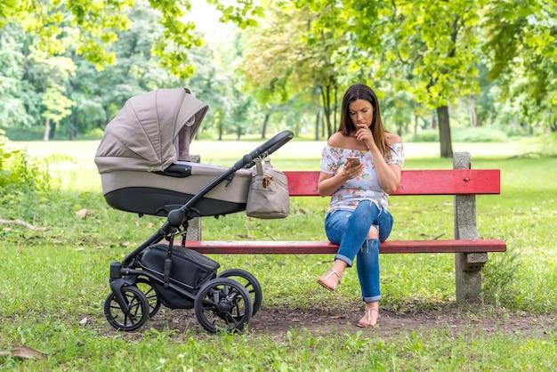 Una madre seria seduta su una panchina e usando il suo smartphone