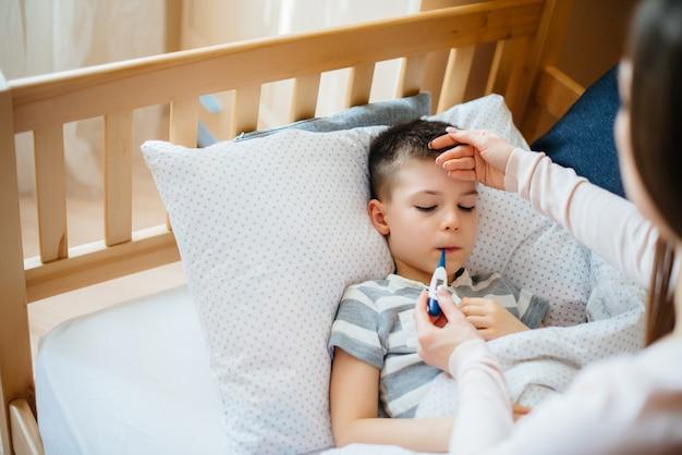 Una madre si prende cura di suo figlio che ha la febbre e la febbre. malattia e assistenza sanitaria.