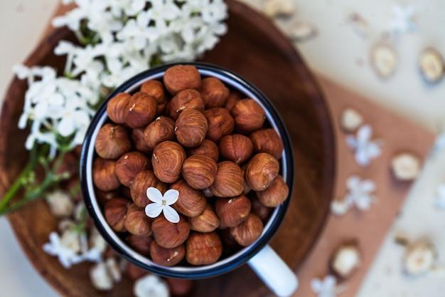 Una manciata di nocciole, nocciole in una tazza su un piatto di legno vista dall'alto, accanto a un ramo con fiori lilla bianchi. c'è un posto dove inserire il testo sulla destra.