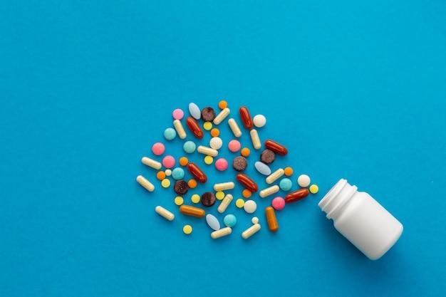 Una manciata di pillole colorate si rovesciò dalla lattina. concetto medico