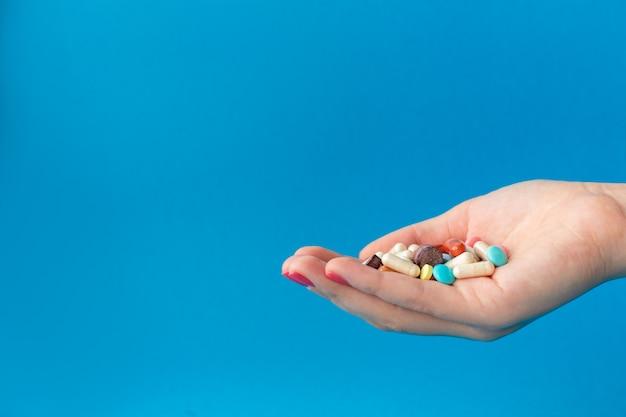 Una manciata di pillole colorate sul palmo. concetto medico. shopping in farmacia.