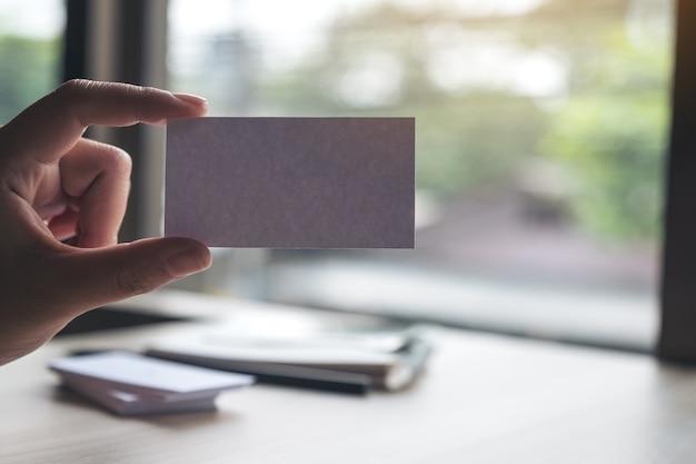 Una mano che tiene e che mostra un biglietto da visita vuoto in ufficio
