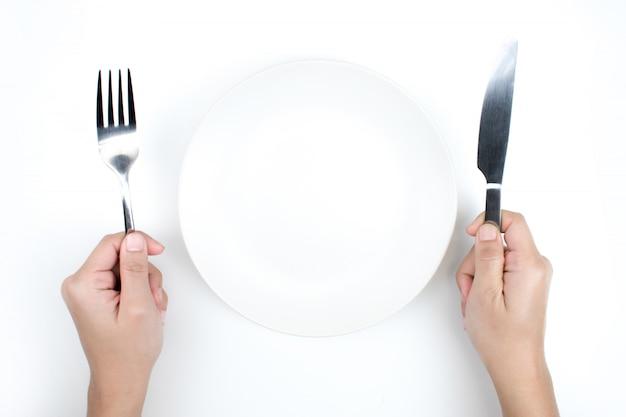 Una mano che tiene un cucchiaio e un piatto vuoto