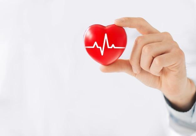 Una mano che tiene un cuore rosso con la linea di ecg.