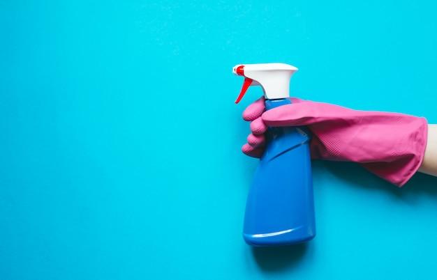Una mano con manicotto in gomma rosa in possesso di uno spray per la pulizia su sfondo blu con vista dall'alto con spazio di copia flat lay.