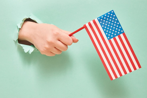 Una mano da un buco nel libro verde detiene una bandiera americana con stelle blu. concetto di festa dell'indipendenza dell'america.
