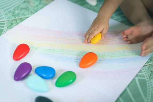 Una mano del neonato asiatico che disegna le linee e forme con i pastelli variopinti.